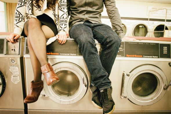 Two people sitting on a laundry machine